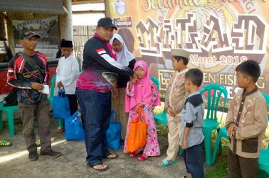 Menyerahkan sembako dan uang kepada anak yatim